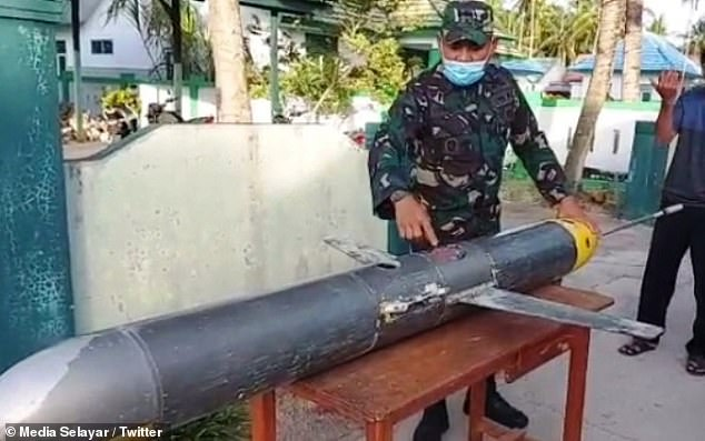 The UUV was reported to authorities and was being inspected by the Indonesian military. Local media shared pictures of officers posing with the submarine drone (pictured)