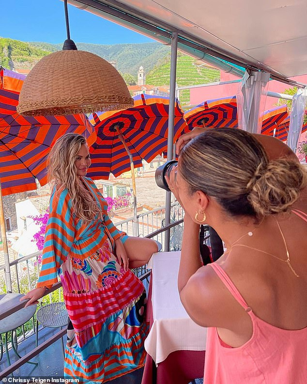 Fashion forward: Chrissy's electric teal and orange Rianna + Nina robe matched a few of the colorful umbrellas scattered on the hillside of the popular coastal retreat