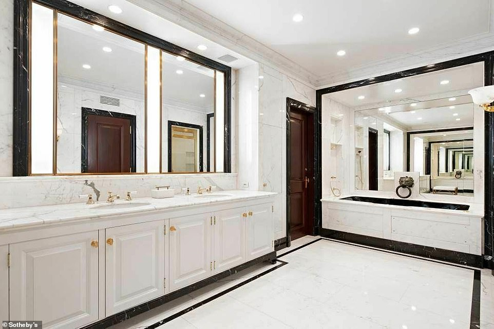 Lots of light: The primary powder room is complete with white cabinetry and gold fixtures