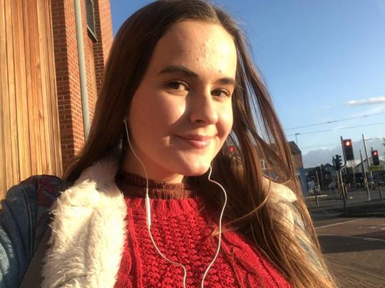Lauren Mcgaun in the sun wearing headphones