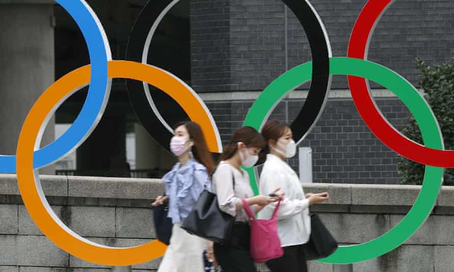 People wearing masks walk in front of a sign comprising the Olympic rings