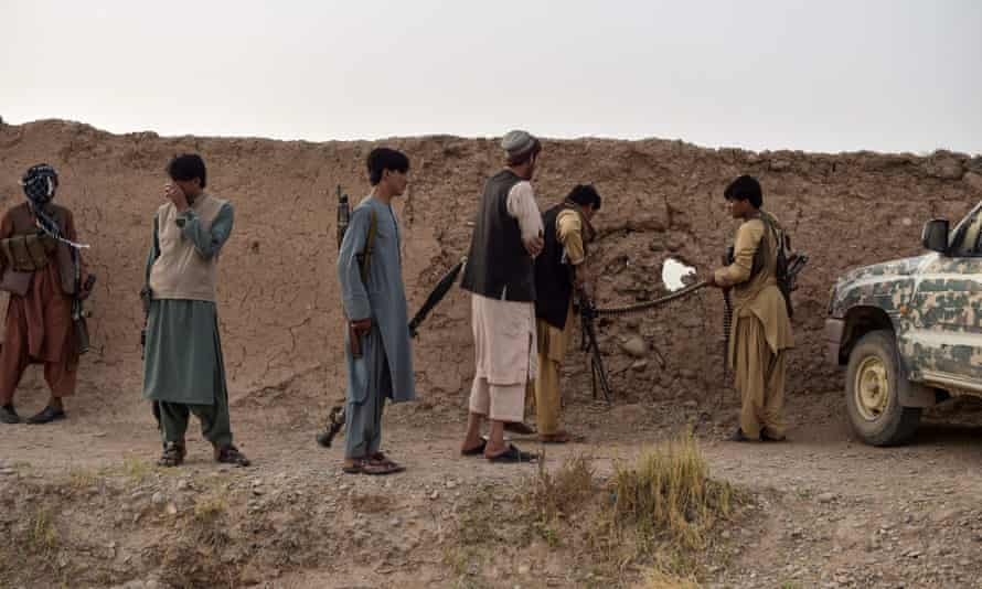 Members of an anti-Taliban militia take position during fighting with Taliban insurgents earlier this year