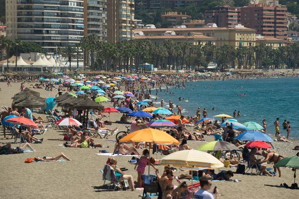 Bathers seen sunbathing at Malagueta beach during a hot summer day in Malaga