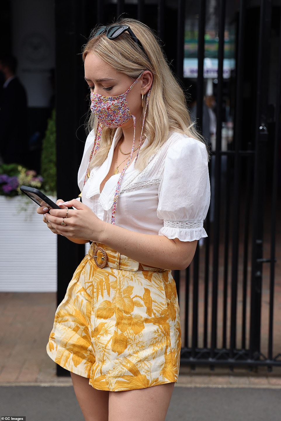Precautions: Tanya made sure to put safety first by wearing a pretty pink floral face covering as she looked at something on her phone