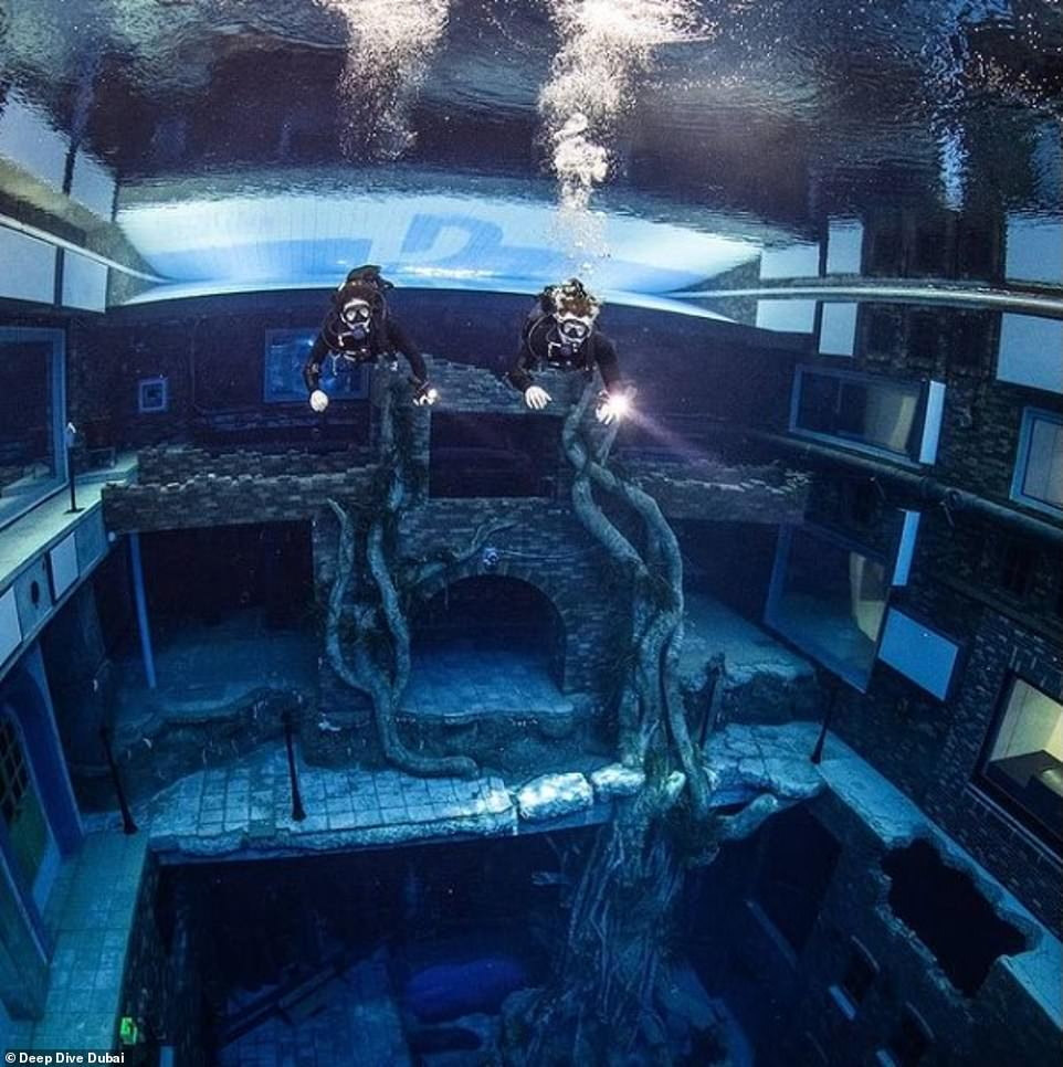 Two divers wearing snorkels explore the underwater city at the latest Dubai attraction, set to open at the end of the year