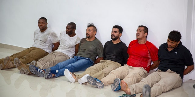 Suspects in the assassination of Haiti's President Jovenel Moise, among them Haitian-American citizens James Solages, left, and Joseph Vincent, second left, are shown to the media at the General Direction of the police in Port-au-Prince, Haiti, Thursday, July 8, 2021. Moise was assassinated in an attack on his private residence early Wednesday. (AP Photo/Joseph Odelyn)
