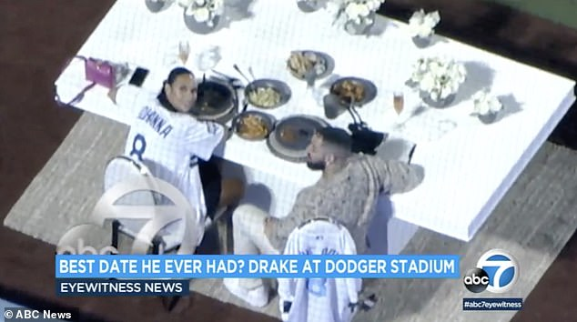 Romantic:The news chopper snapped a photo of Drake and the social media influencer sitting at a large white table covered with several bouquets of flowers with dinner plates in front of them and glasses of rose champagne