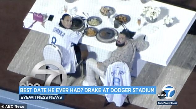 Iconic date night:Drake appeared to be wearing a neutral toned sweater while Johanna opted to wear her new custom Dodger's jersey with slicked back hair and a long braid