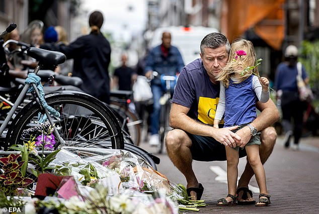People leave flowers, candles and messages of support to Peter R. de Vries in the Lange Leidsedwarsstraat in the center of Amsterdam