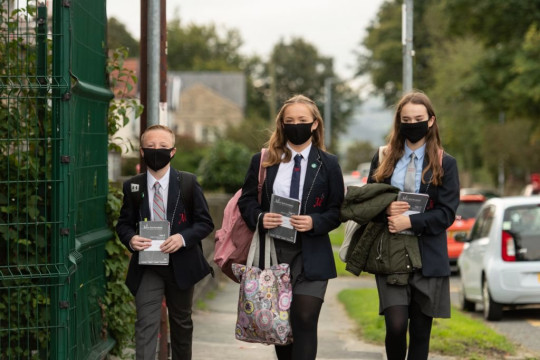 Pupils wearing facemasks as a precaution against the transmission of the novel coronavirus arrive to attend Moor End Academy in Huddersfield, northern England on September 11, 2020. - Millions of children across England have returned to school after the Covid-19 lockdown with many schools introducing measures to enable as safe an environment as possible. (Photo by OLI SCARFF / AFP) (Photo by OLI SCARFF/AFP via Getty Images)