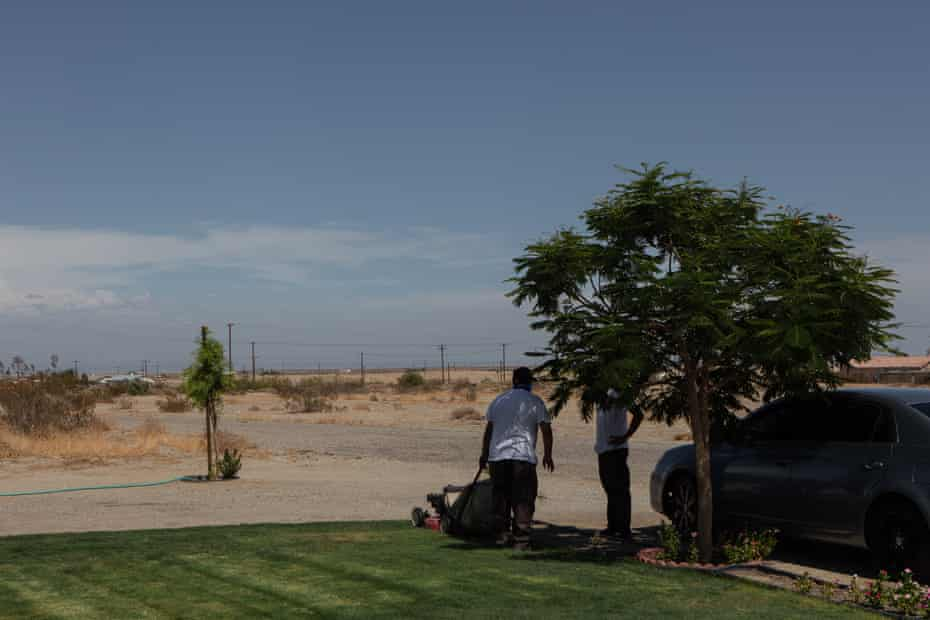 A man mows his lawn in the afternoon heat in Salton City.