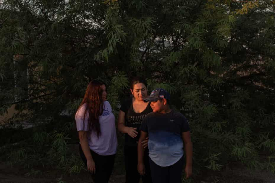Nancy del Castillo stands with her daughter and son in the shadows of a large tree.