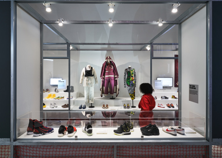 A visitor looking at the Sneakers Unboxed exhibtion. On display are sneakers and clothes in glass boxes