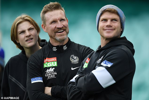 U-turn: Nathan (pictured with his sons at his last Collingwood game as coach) later ended the heated debate by urging everyone to be kind to one another