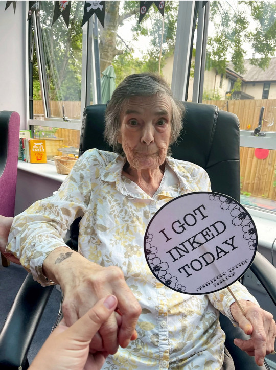 Care home residents took part in an ?inking and drinking? day ? where they all got makeshift tattoos and drank booze. See SWNS story SWBRtattoo. Castleford House handed out stick on tattoos for around 15 residents, along with complimentary bottles of Corona. The care home put on the fun event on July 11 after one resident said they?d always wanted a tattoo. Others had also regularly complemented Head of Lifestyles Amelia Pace ? who herself has tattoos. Amelia, who?s been working at the home for seven years, came up with the idea for tattoos and booze to bring some joy to the home, and says it was a big success.
