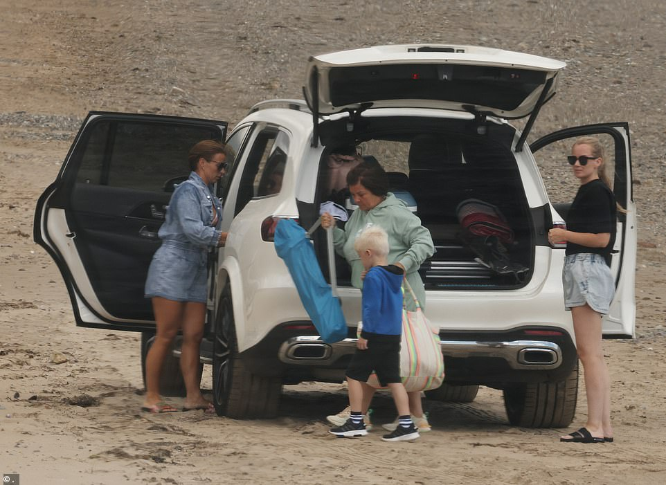 The whole gang: Coleen was joined by her mum, kids and a companion as they unloaded the car