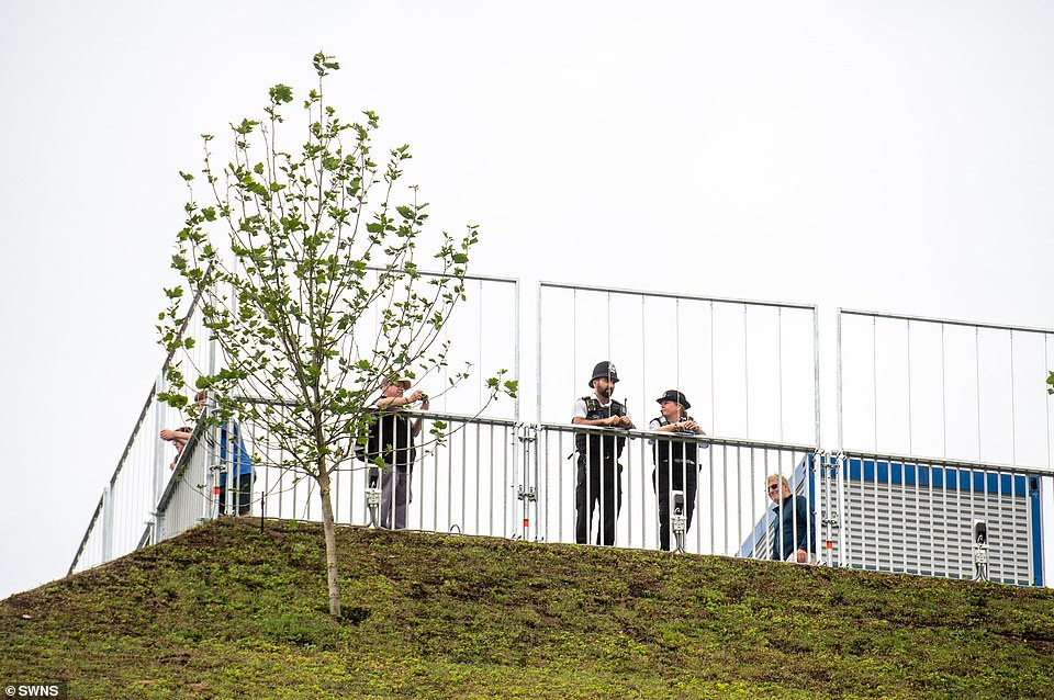 Policemen join members of the public at the top of the mound, which is fenced off - for safety reasons
