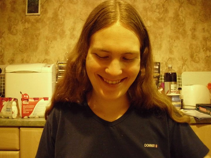Helen is pictured sitting in a kitchen, smiling but with her gaze looking down