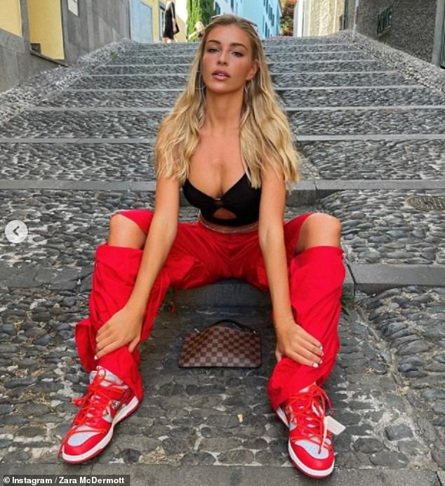 Sizzling:Just hours earlier, the star also showed off her washboard abs in a skimpy black crop top and red combat trousers as she shared a glimpse of her latest shoot on a street in Madeira