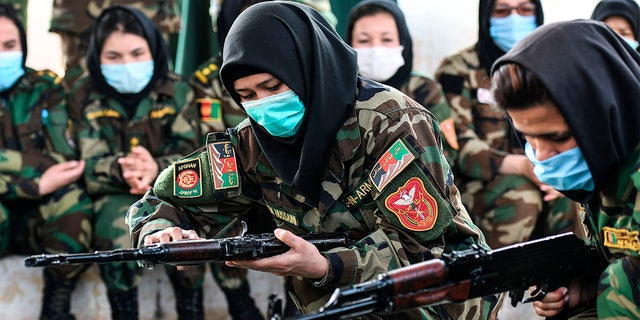 Afghan women cadets handle an AK-47 rifle during a training program at the Officers Training Academy in Chennai on February 18, 2021. (Photo by Arun SANKAR / AFP) (Photo by ARUN SANKAR/AFP via Getty Images)