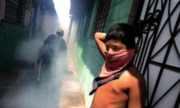 A child protects himself as sanitation workers fumigate San Salvador's El Campito slum to kill mosquitoes.