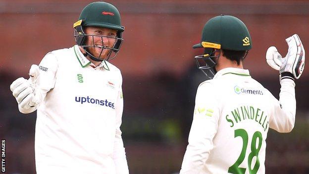 Ed Barnes and Harry Swindells celebrate a batting milestone at Somerset