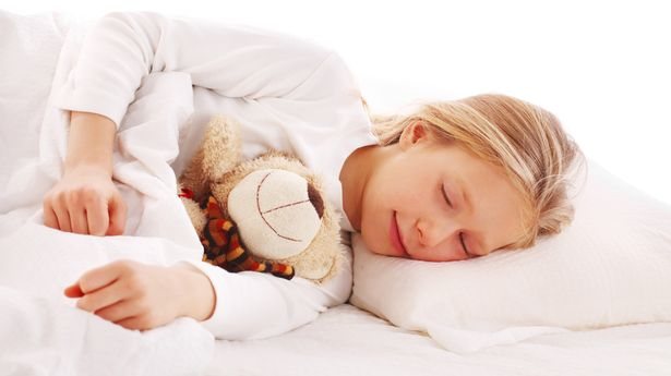 Cute little blonde girl sleeping in bed with her teddy.