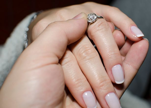 Close-up of groom placing wedding band on his bride's finger during the wedding ceremony.