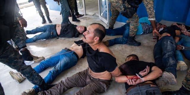 Suspects in the assassination of Haiti's President Jovenel Moise sit on the floor after being detained, at the General Direction of the police in Port-au-Prince, Haiti, Thursday, July 8, 2021. A Haitian judge involved in the murder investigation said that President Moise was shot a dozen times and that his office and bedroom were ransacked. (AP Photo/Jean Marc Hervé Abélard)