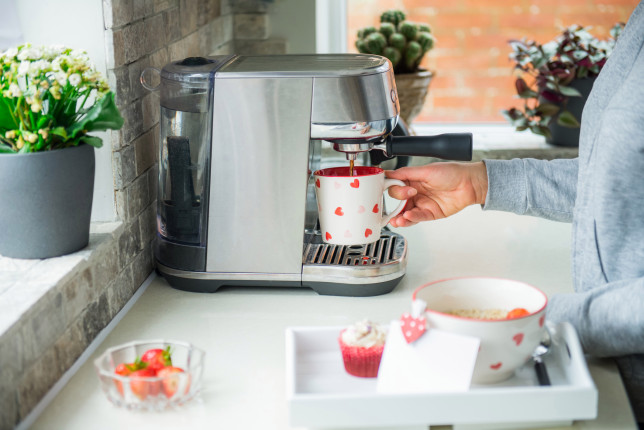Woman making coffee on machine during preparing a surprise breakfast for lover on Valentines' day. A tray with oatmeal porridge with strawberries, cupcake, and blank greeting card on table. Copy space