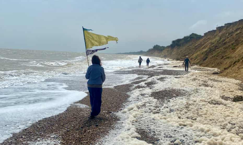 Walking on the coast south of Lowestoft. The spume is generated by algae in the water