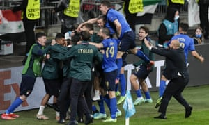 Italy's Jorginho is congratulated by teammates after scoring the winning penalty