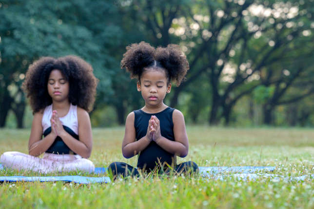 Afro American cute children in sportware is meditating on yoga mat outdoor. Sport, Healthy lifestyle, Children learnling outdoor concept.