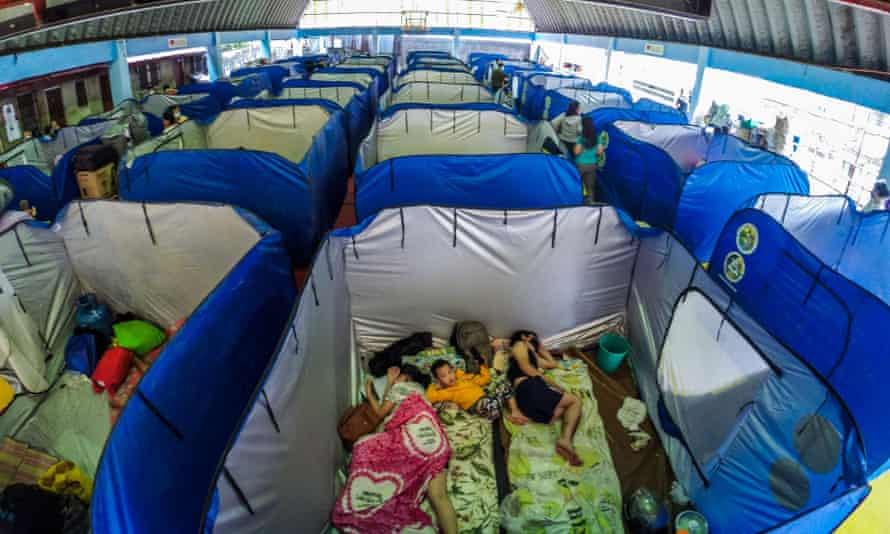 Families take shelter inside emergency tents at an evacuation centre in Marikina.
