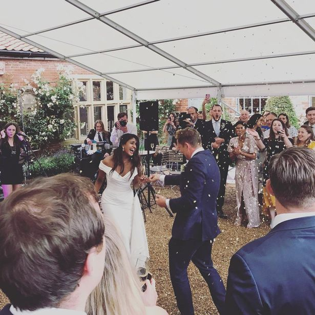 Simon and Derrina were welcomed back at their reception venue by ecstatic guests who throw petal confetti over them