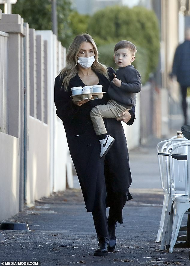 Glamour: WAG Nadia Bartel, 36, (pictured) juggleda carton of takeaway coffees while carrying her son Henley, two, in Melbourne on Tuesday
