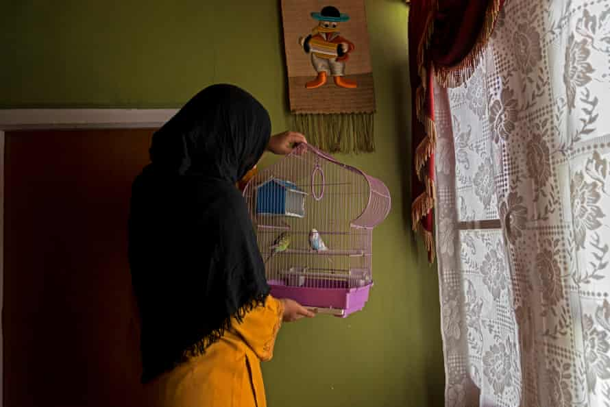 Hafsa plays with birds in a cage, 2021