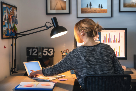 Woman working on computer and digital tablet in her home office during pandemic.