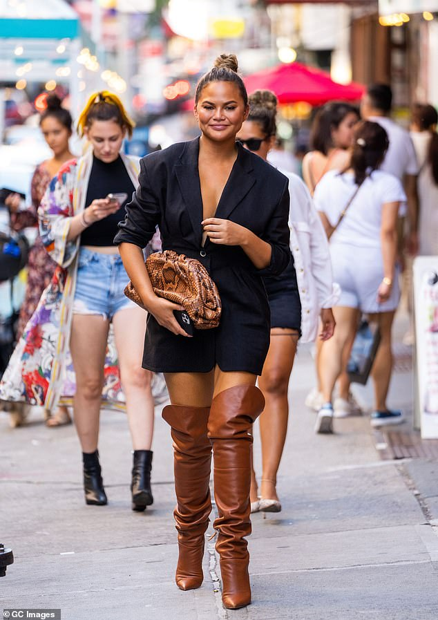 Quick change:Chrissy also showed off multiple ensembles, including a feathered black coat with ripped jeans, while another outfit featured thigh-high brown leather boots with a dress-like blazer that she wore without a top; seen Friday in NYC