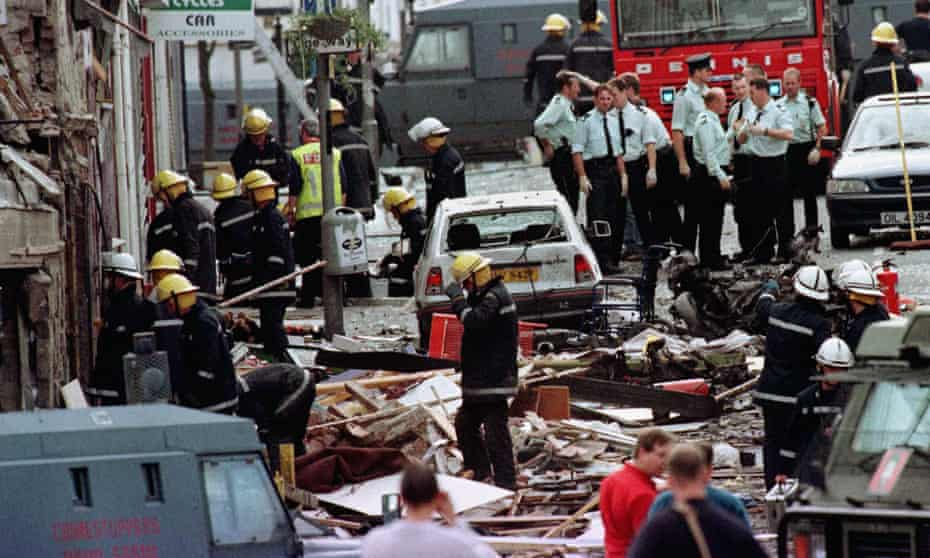 Police and firefighters inspect the damage caused by the explosion in Market Street, Omagh