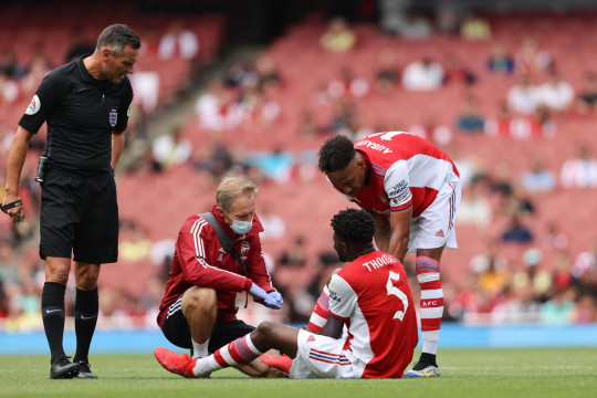 LONDON, ENGLAND - AUGUST 01: Thomas Partey of Arsenal suffers an injury after gets his right foot trapped in a tackle with Hakim Ziyech of Chelsea during Arsenal v Chelsea: The Mind Series at Emirates Stadium on August 1, 2021 in London, England. (Photo by Matthew Ashton - AMA/Getty Images)