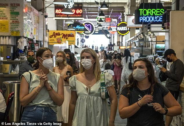 Cities like Los Angeles have reinstituted mask mandates in response to surges of the Delta COVID-19 variant. Pictured: people at Los Angeles' Grand Central Market wear masks indoors