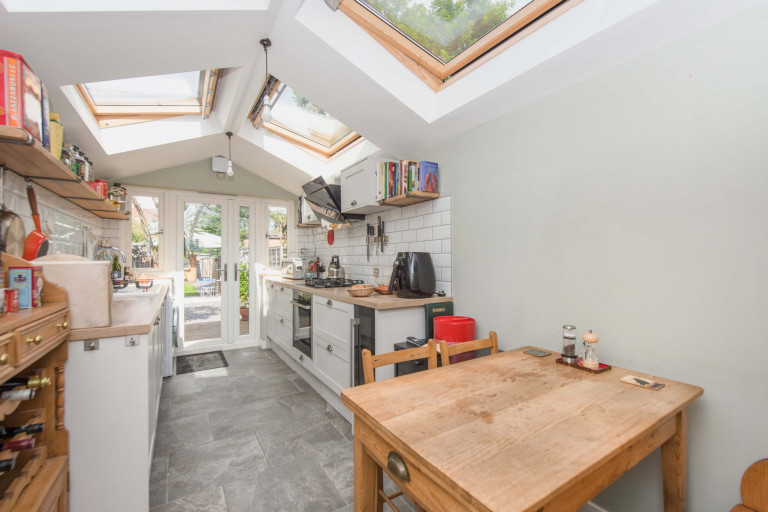A tiny two-bedroom terraced home measuring just 2.4 meters in width for sale in London - kitchen leading to garden