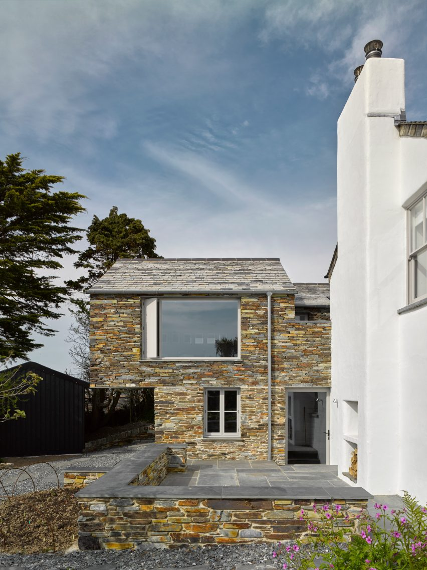 A stone extension to a white house