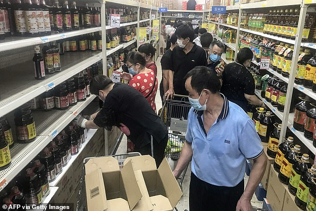 Panic-buying shoppers stripped bare shelves in supermarkets in Wuhan after authorities announced they will test the the entire city for Covid-19 following the first local infections in more than a year