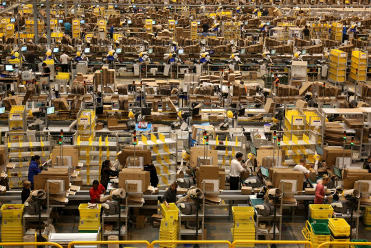 File photo dated 25/11/14 of Amazon workers packing orders on the warehouse floor at the Amazon UK Fulfilment Centre in Peterborough, Cambridgeshire. The retail giant has announced it is to increase its minimum wage to ?10.50 an hour in London and ?9.50 for other parts of the UK. PRESS ASSOCIATION Photo. Issue date: Tuesday October 2, 2018. See PA story INDUSTRY Amazon. Photo credit should read: Chris Radburn/PA Wire