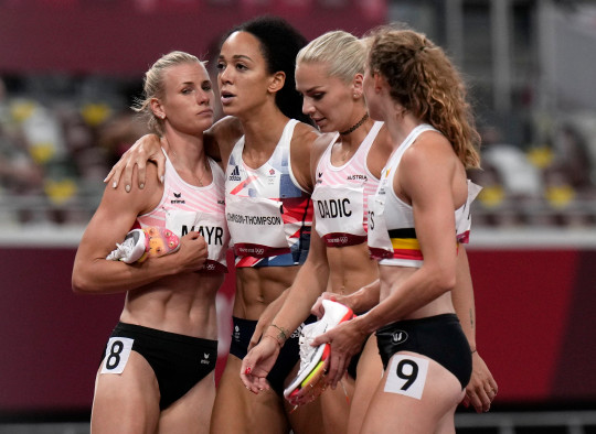 Katarina Johnson-Thompson, of Britain, second left, is consoled by other competitors after pulling up injured in the heptathlon 200-meters at the 2020 Summer Olympics