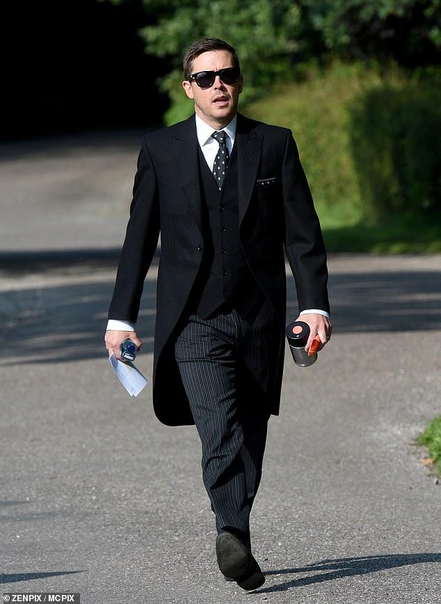 Smart:Gavin Moss looked smart as he strolled around set wearing a pinstripe suit