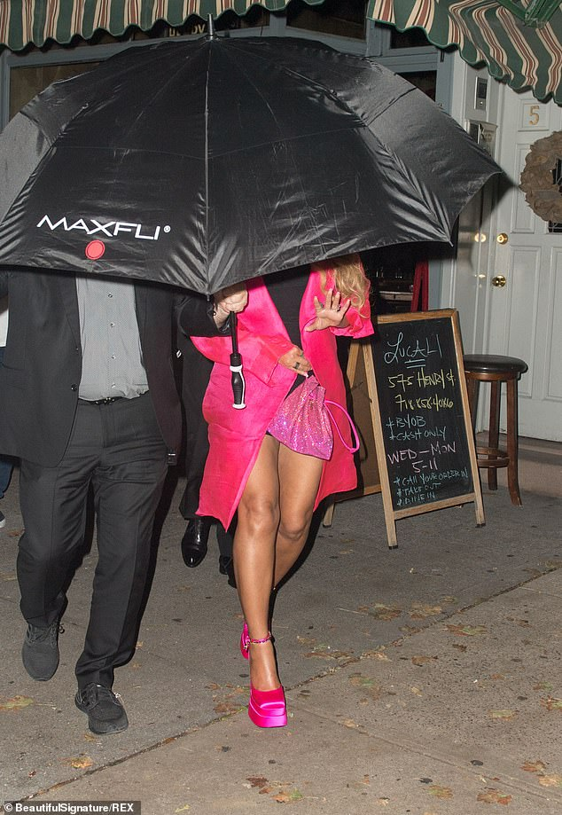 Coming through! Beyonce was shielded by a security guard holding an umbrella
