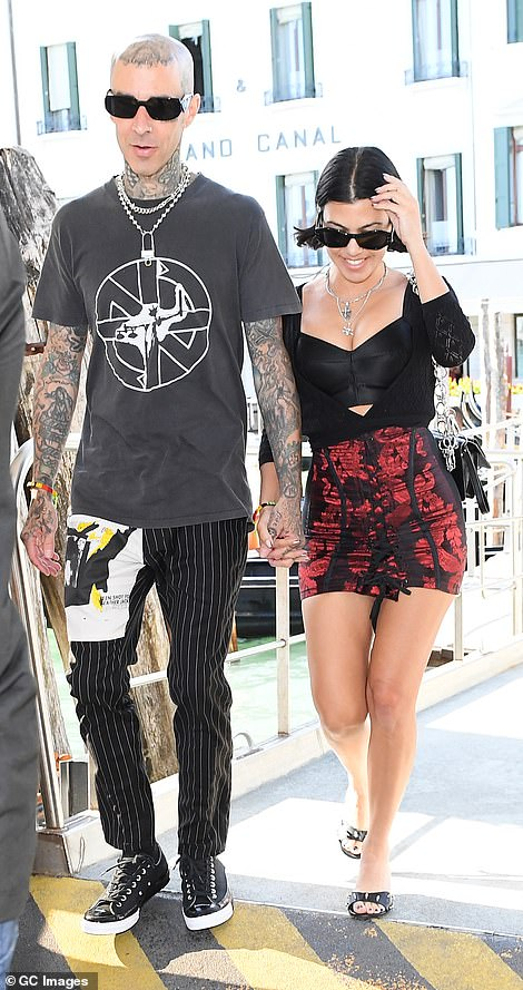Perfect match:Kourtney Kardashian flashed her toned legs in a black floral miniskirt as she caught the Venetian sights with her dressed-down beau Travis Barker on Sunday